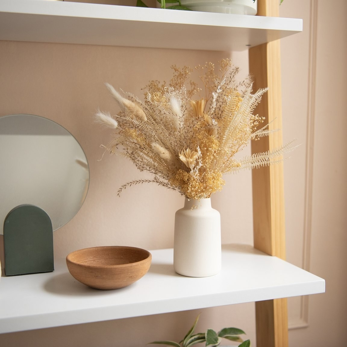 the neutral bouquet in its vase on a display shelf
