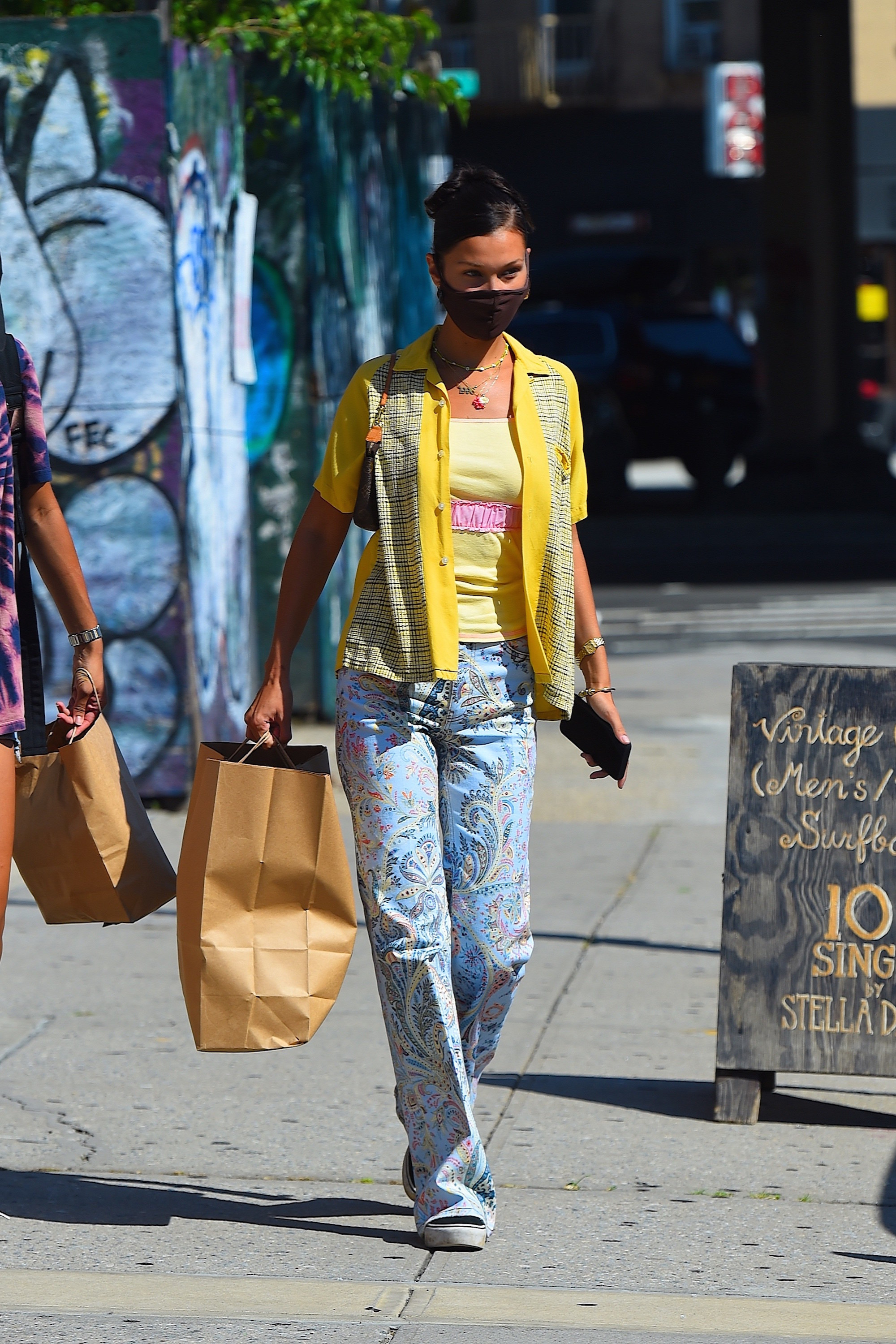 Bella Hadid in a yellow shirt and patterned pants