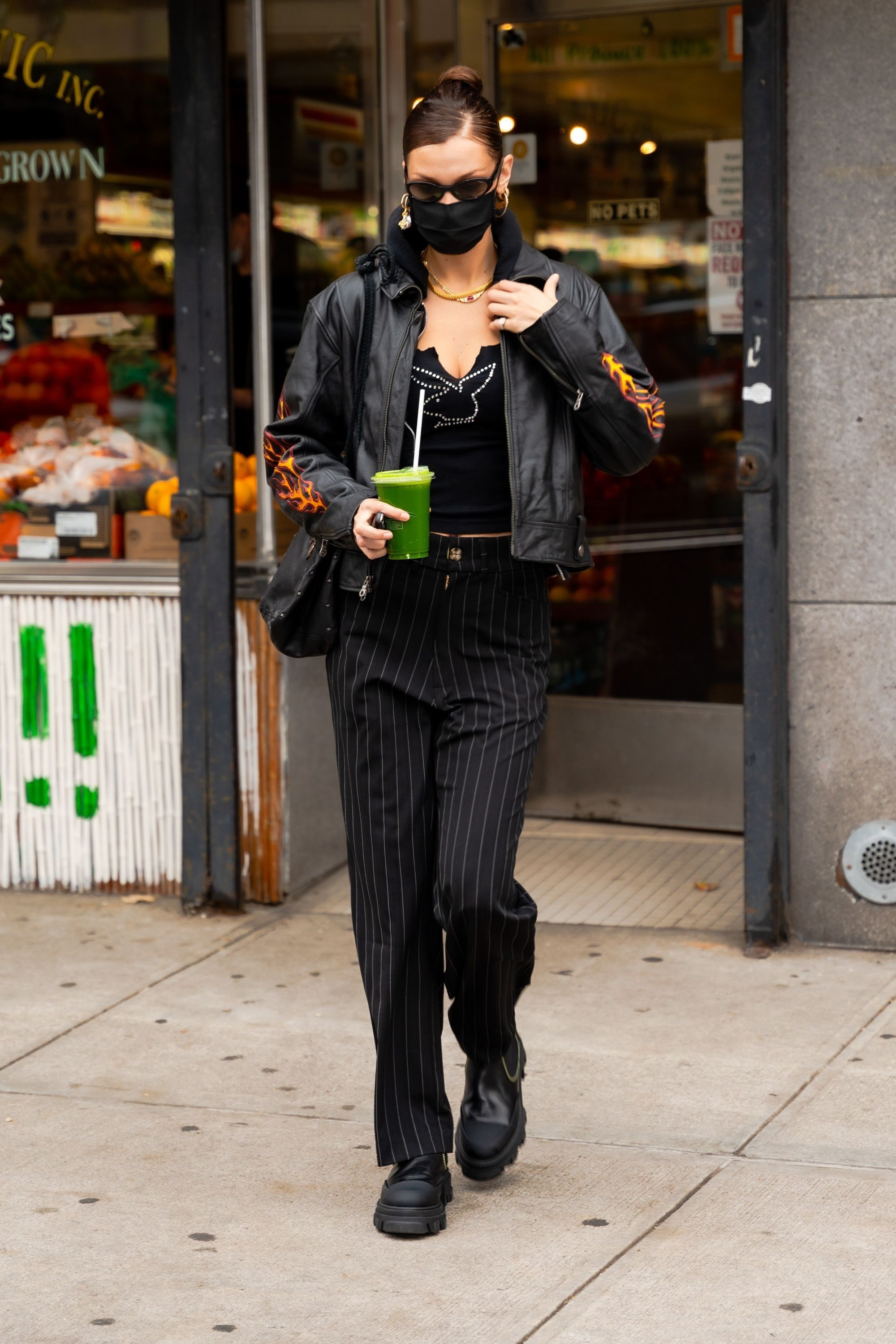 Bella Hadid in a leather jacket and striped pants holding a green juice