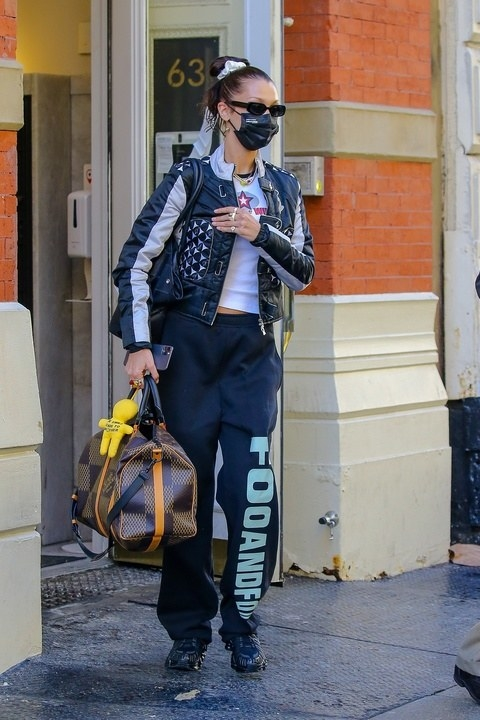 Bella in a studded jacket, a t-shirt and sweatpants carrying a duffle bag