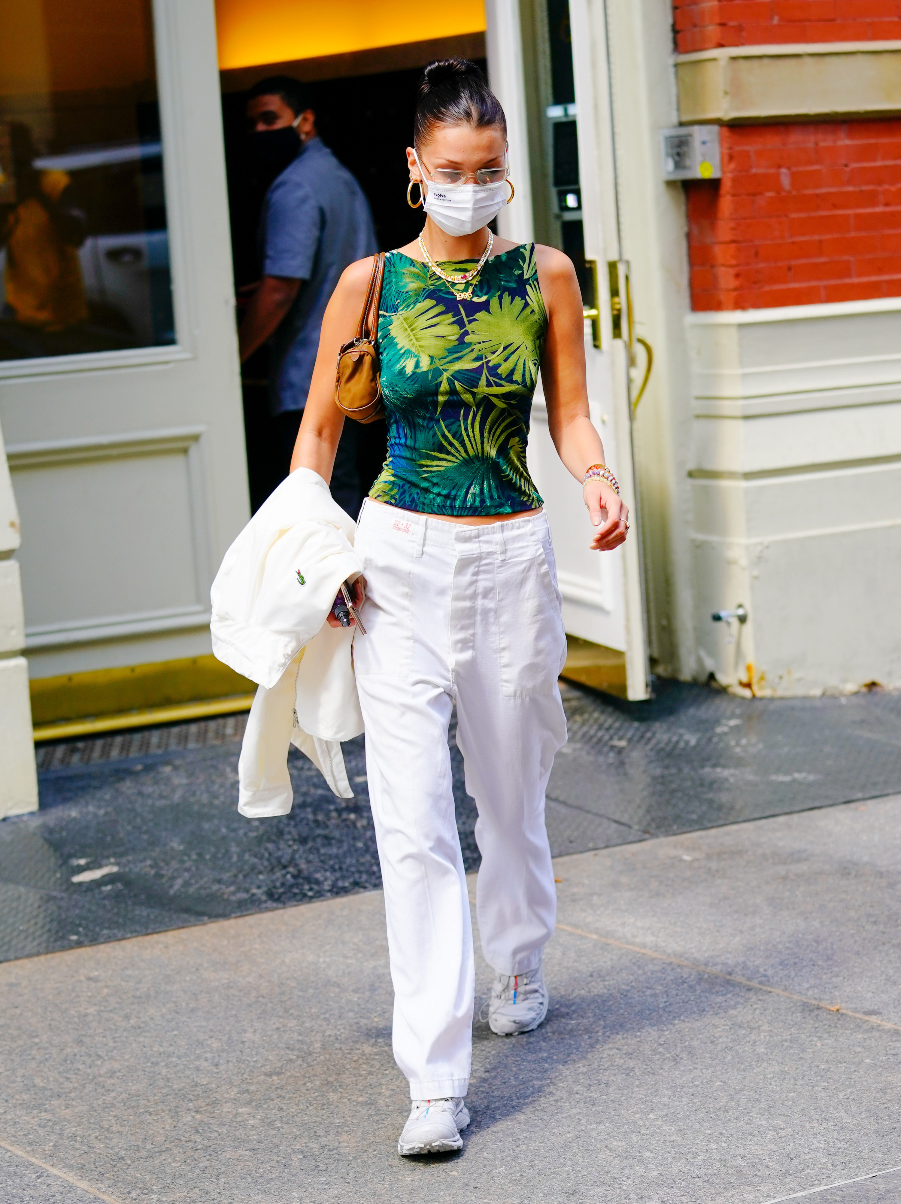 Bella wearing white jeans, sneakers and a printed tank top