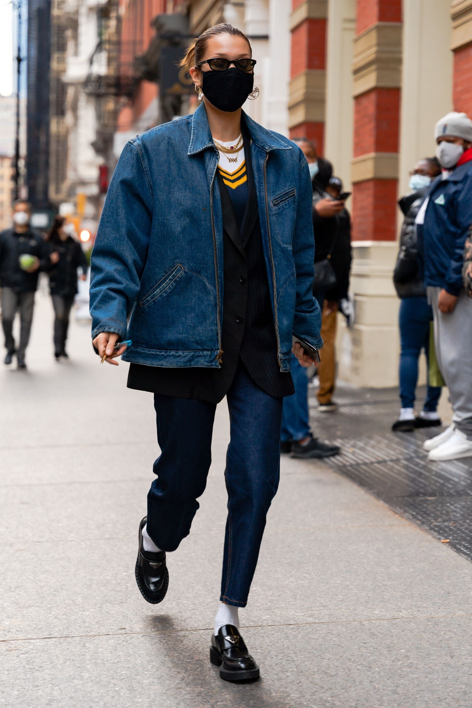 Bella Hadid in jeans, a sweater vest and an oversized jean jacket