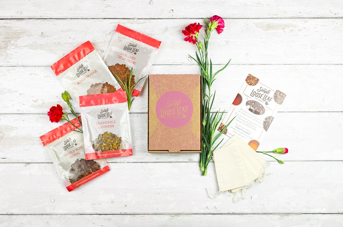 the subscription box and four pouches of tea on one side with a card with tea notes on the other side and a carnation flower laying beside it all. sigh. so beautiful.