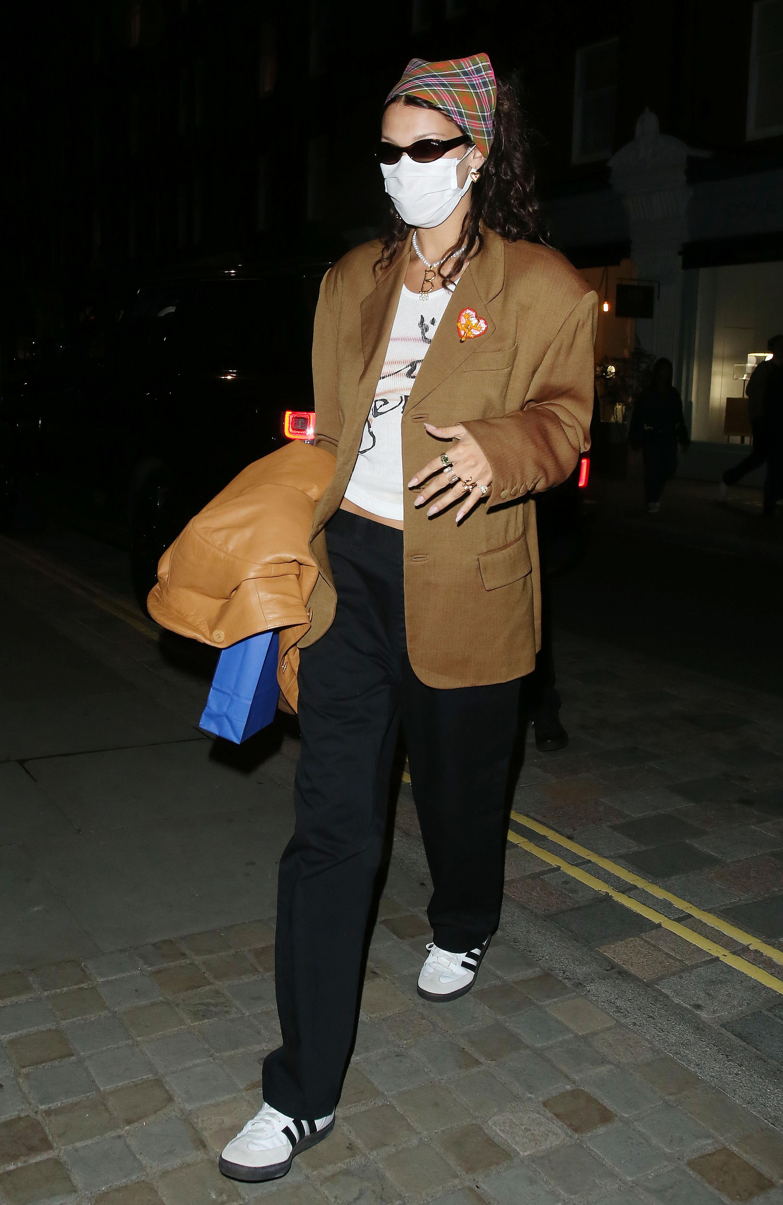 Bella in a plaid headband, a tan blazer and black low rise pants
