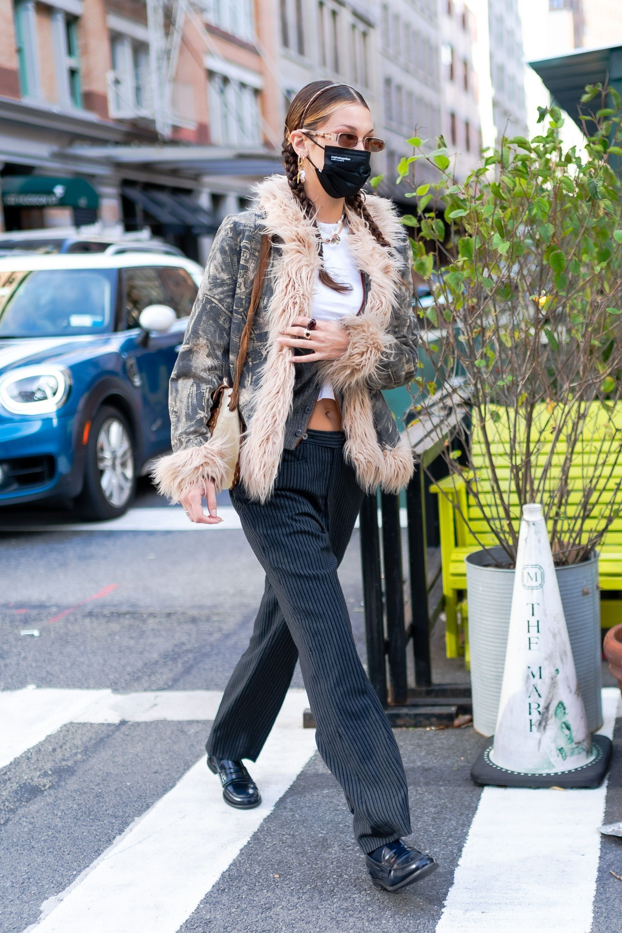 Bella Hadid in a camo jacket and striped pants
