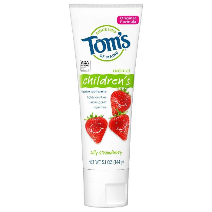 White toothpaste tube with smiling strawberries on it
