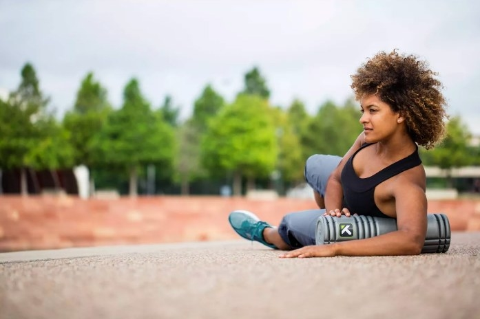 Model using the foam roller to stretch her abdomen and shoulders
