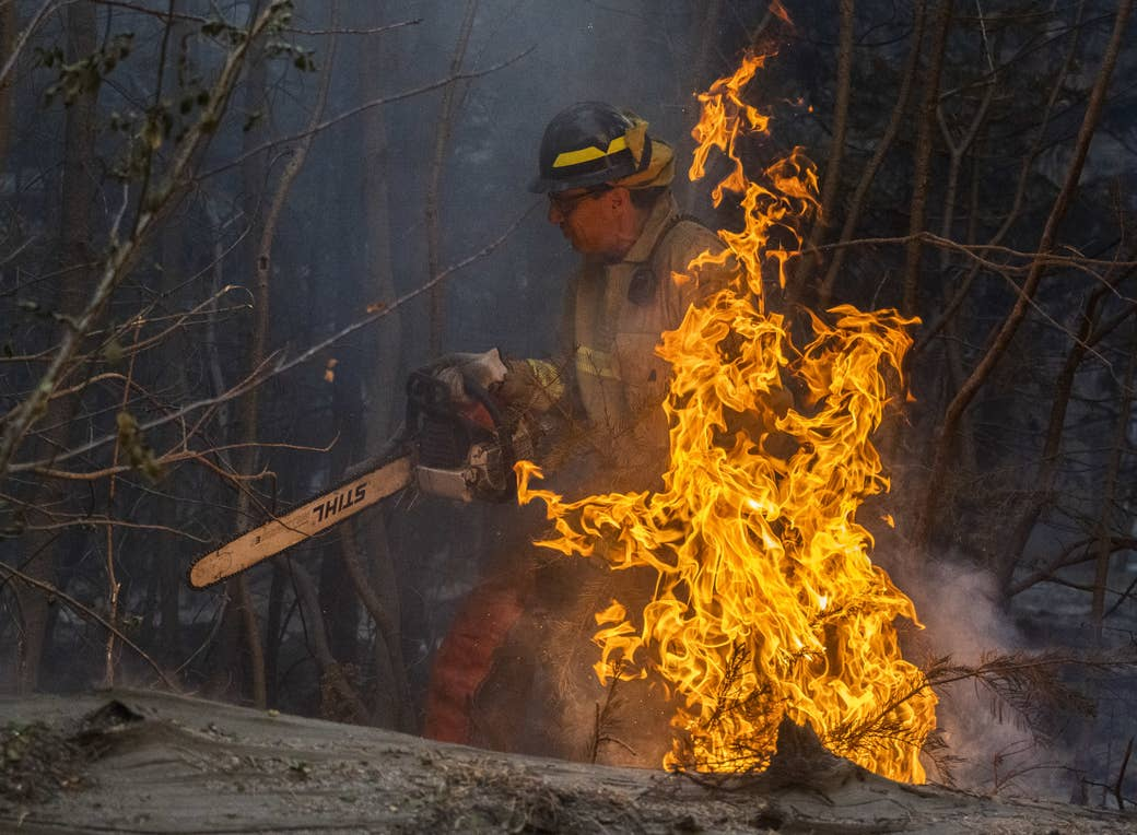 Martin Goldberg is shown in fire gear with a chainsaw as flames burn in front of him
