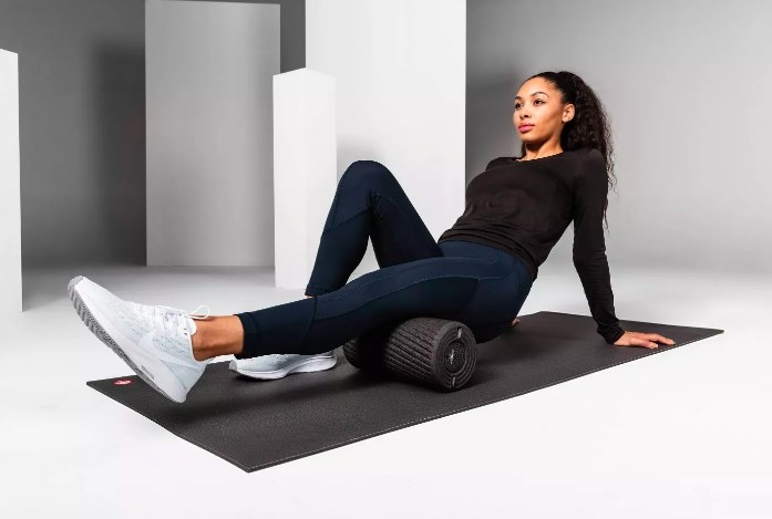 A model using the vibrating foam roller on her hamstring
