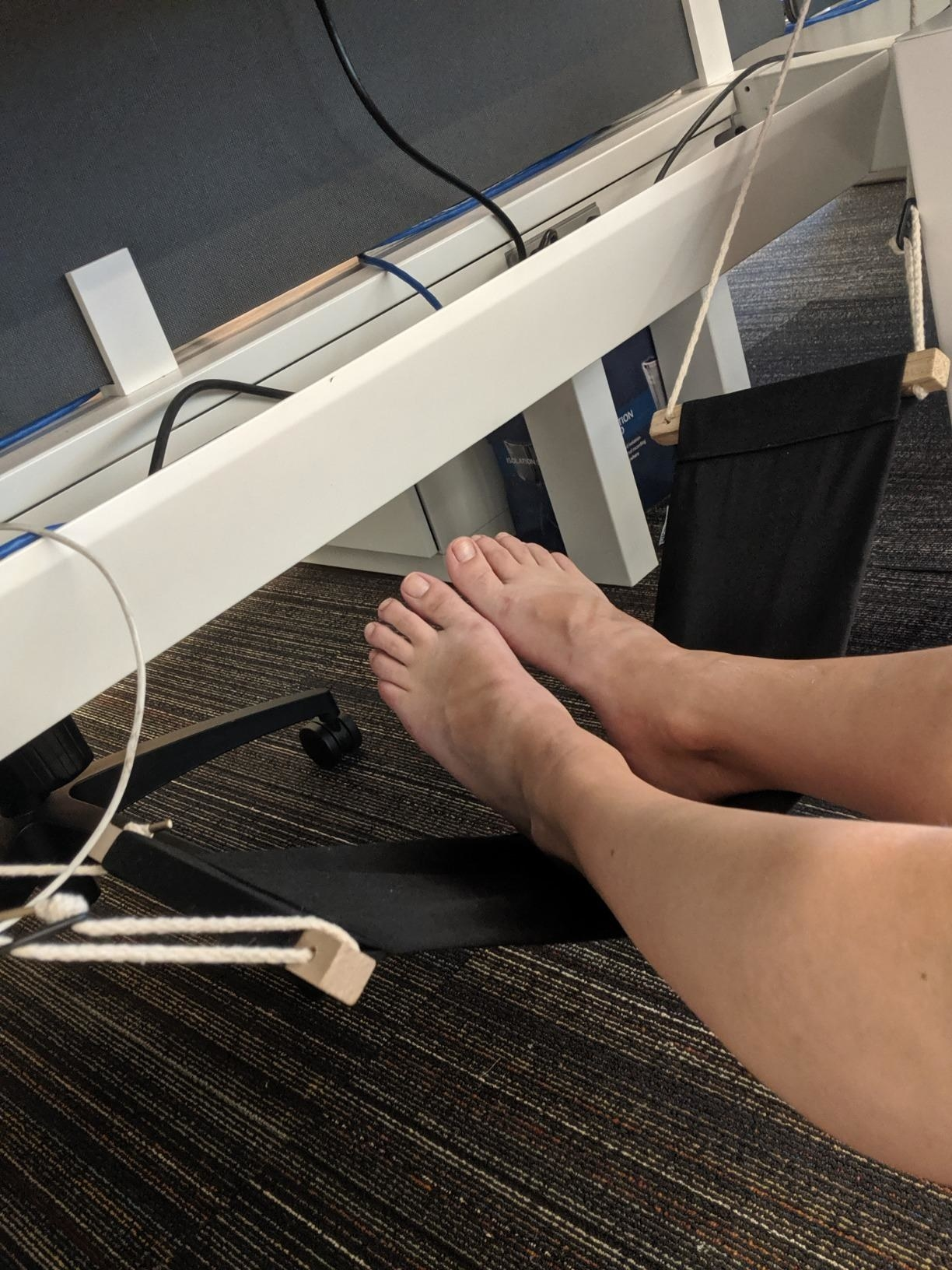 a reviewer with their feet resting on the hammock under their desk setup