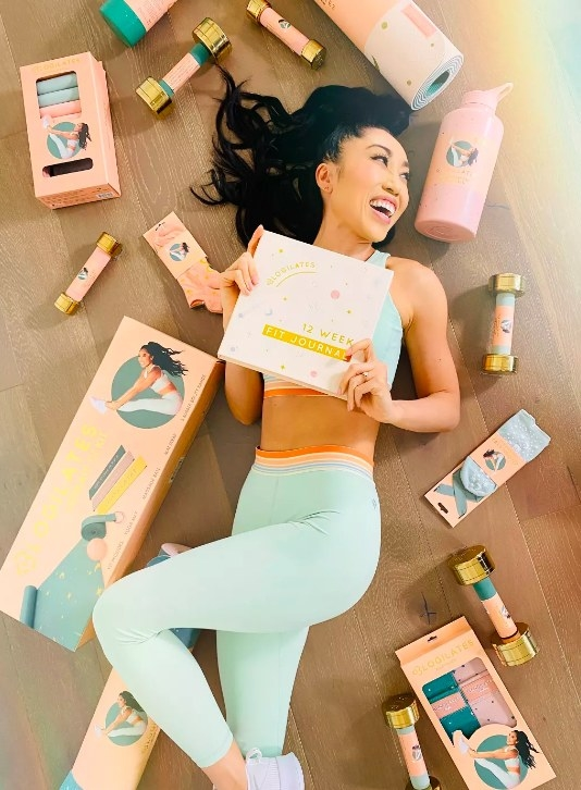 Model laying on ground surrounded by blogilates exercise equipment