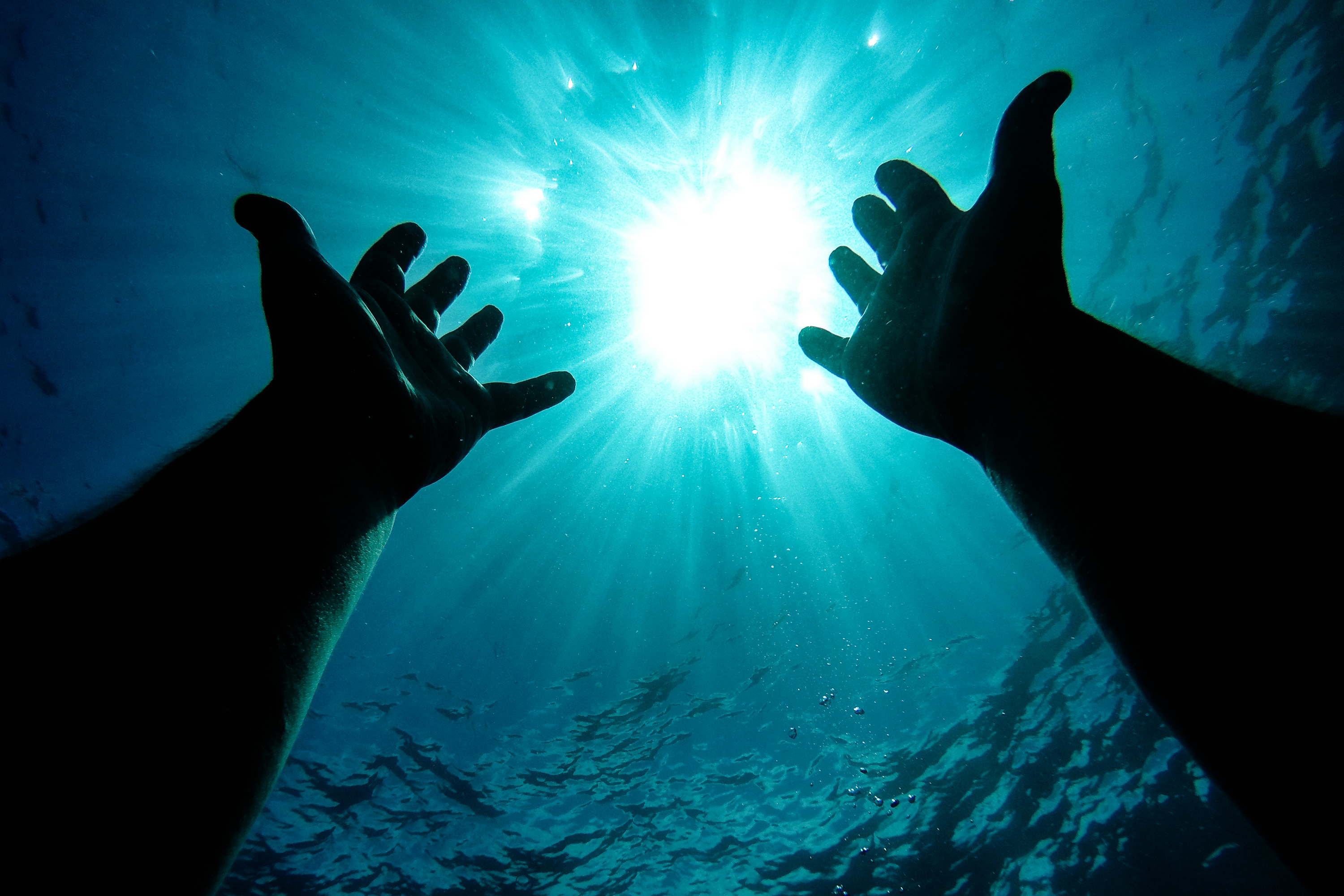 Two hands reaching for the surface under water