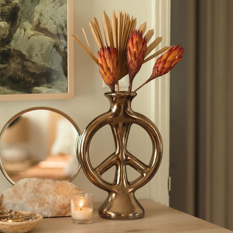 peace shaped vase in gold with flowers inside