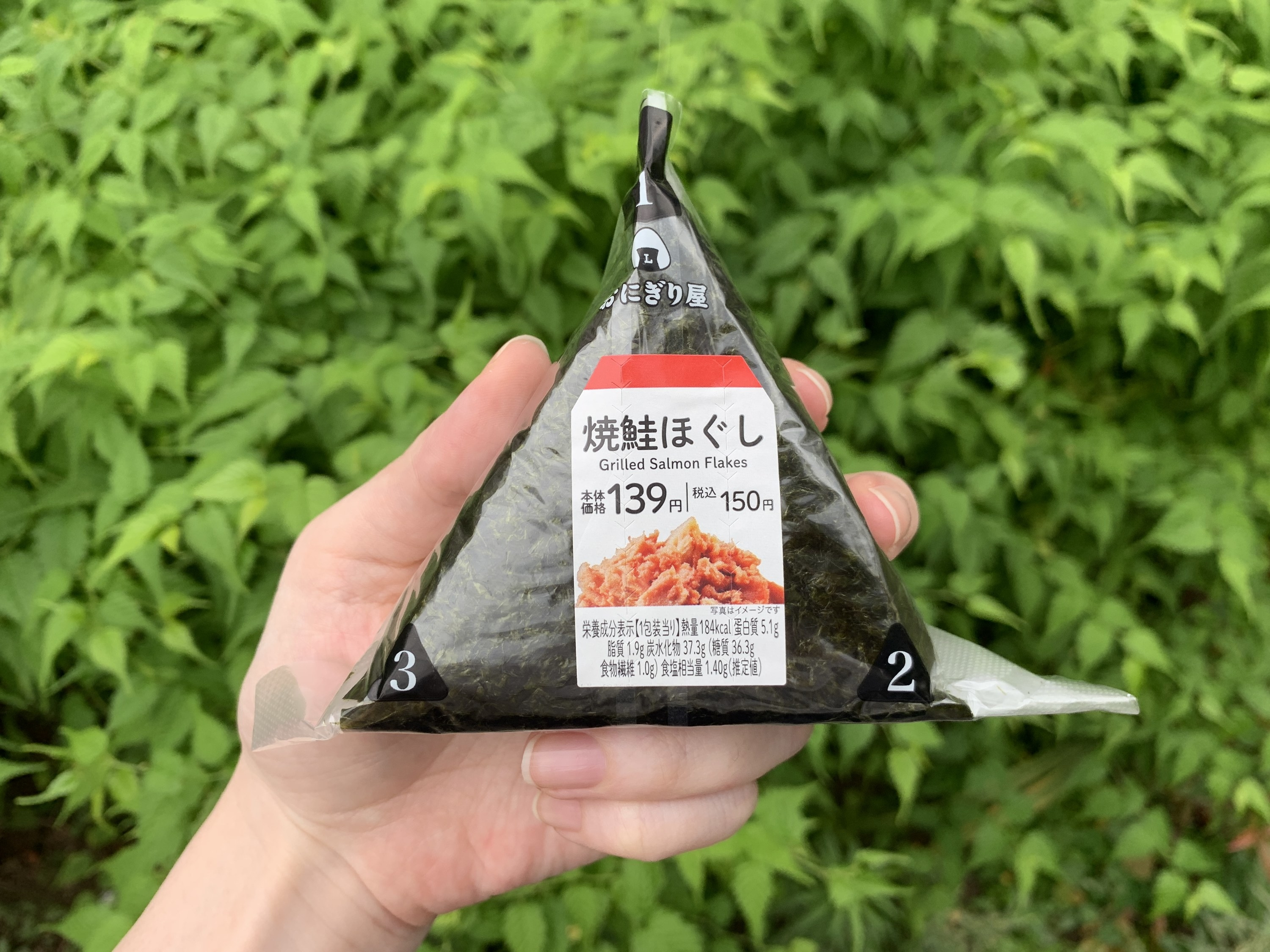 A hand holding a packaged onigiri