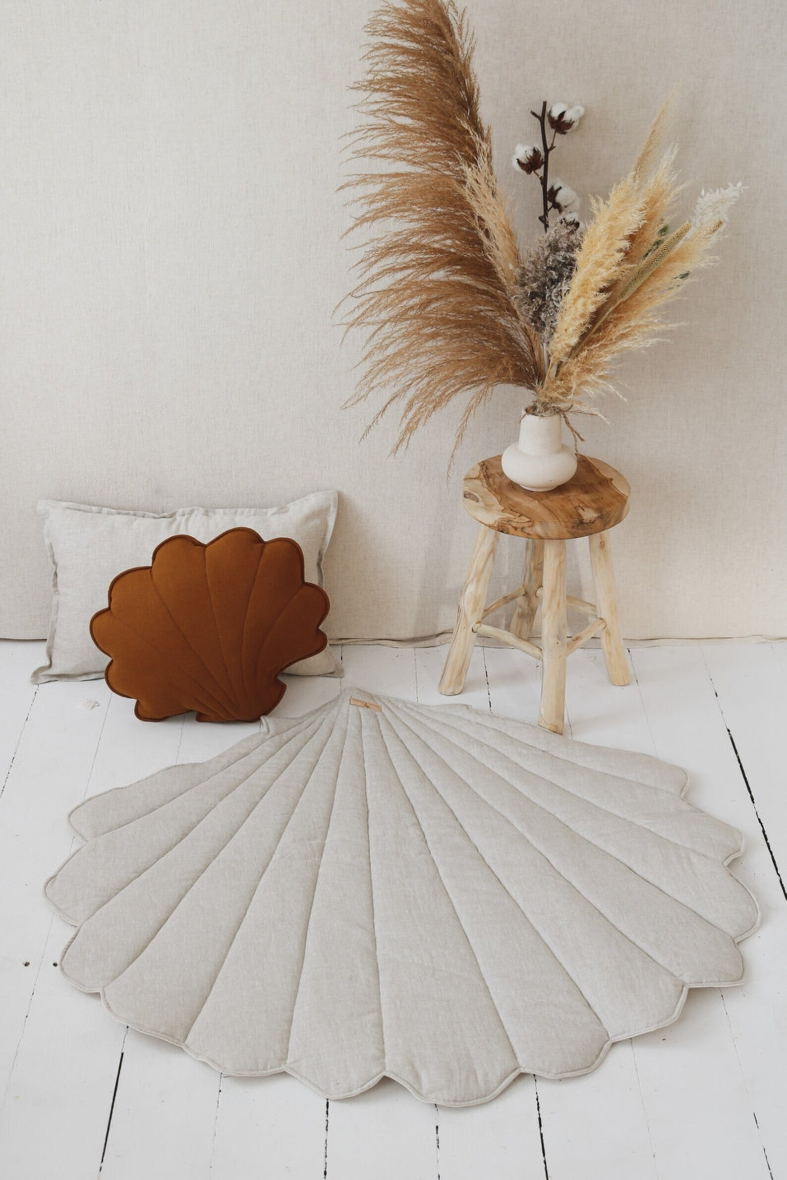 sea shell shaped mat on wooden floor. it's beside matching pillows and dried flowers.