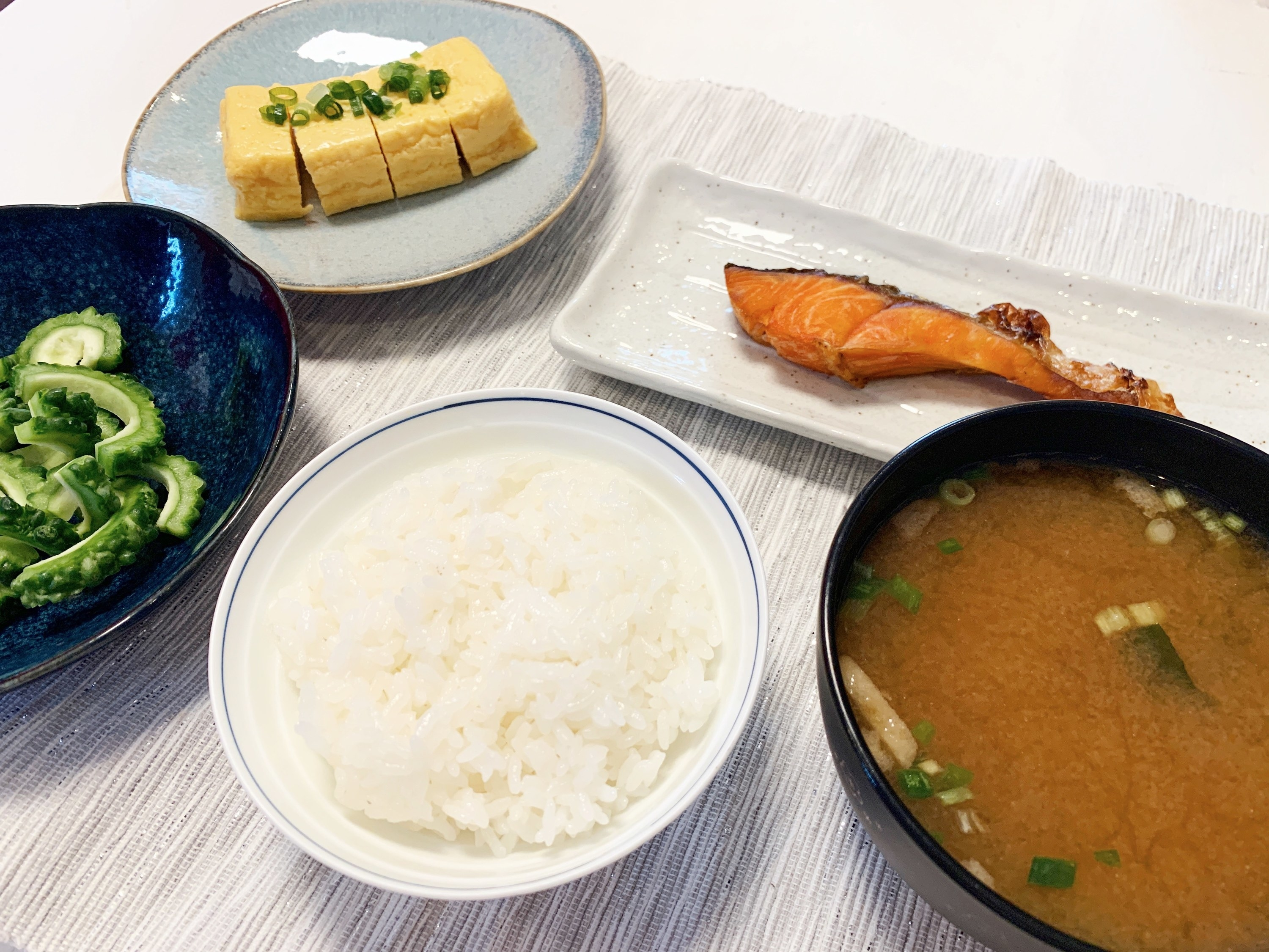 Several bowls on a table – they are filled with rice, miso soup, grilled salmon, Japanese omelette and vegetables
