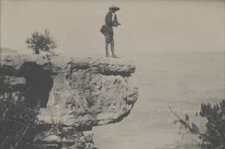 A person in a hat stands on a ledge overlooking the grand canyon, holding a camera