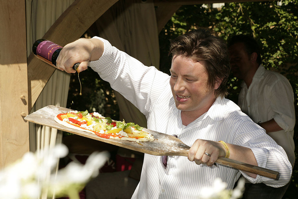 Jamie Oliver dresses a pizza with olive oil
