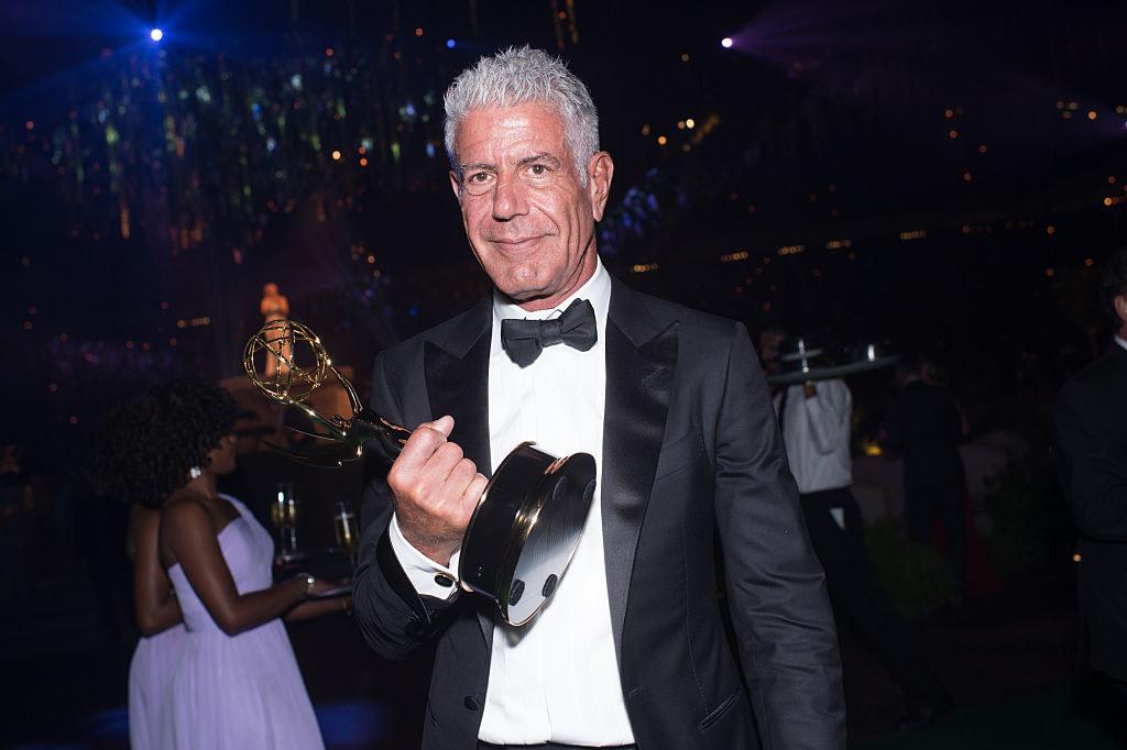 Anthony Bourdain holding an Emmy