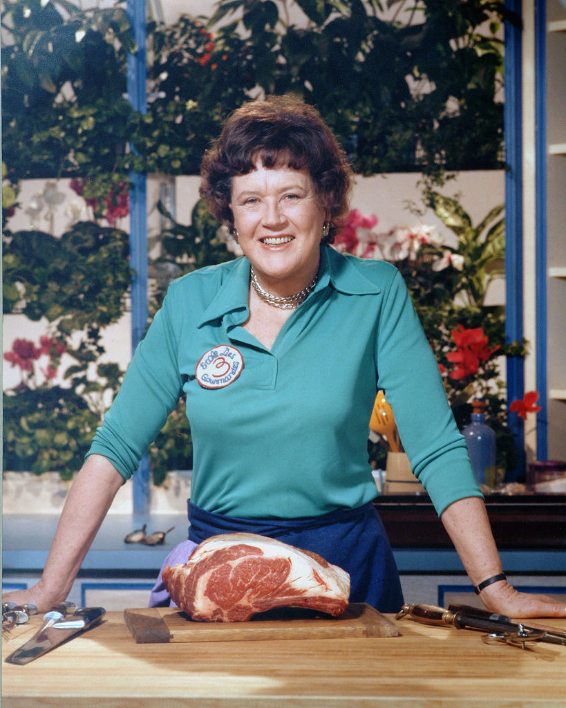 Julia Child standing over a piece of meat