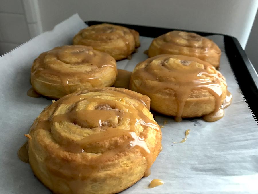 Five pumpkin cinnamon rolls on a baking sheet, covered in pumpkin spice glaze
