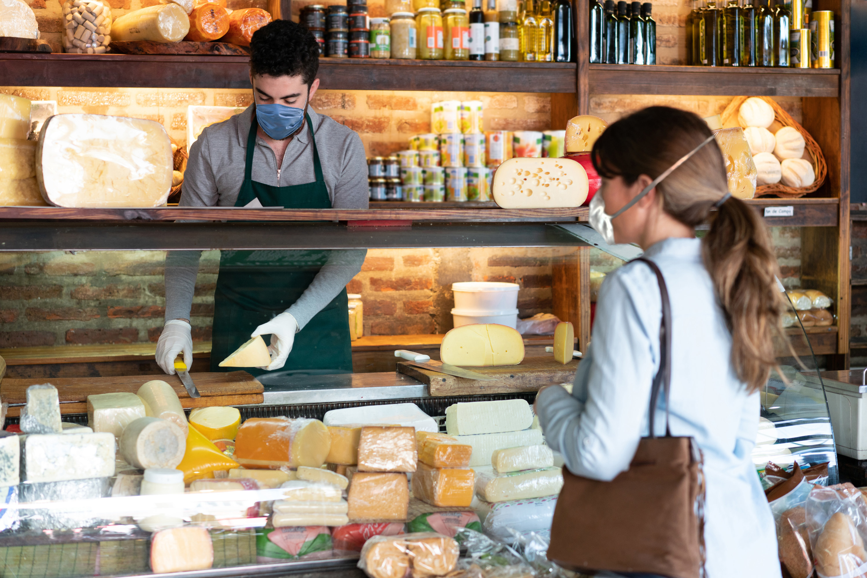 Woman buying cheese at a fancy cheese store