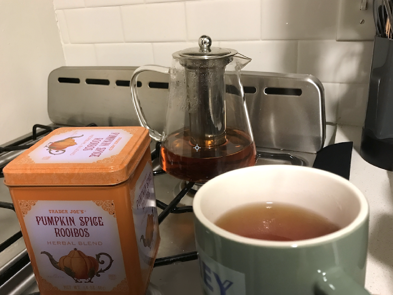 A tea pot with tea in it, the pumpkin spice rooibos container, and a mug of tea