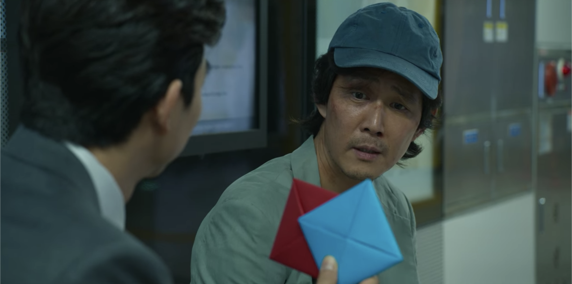 The man holding up two cards in Gi-hun's face