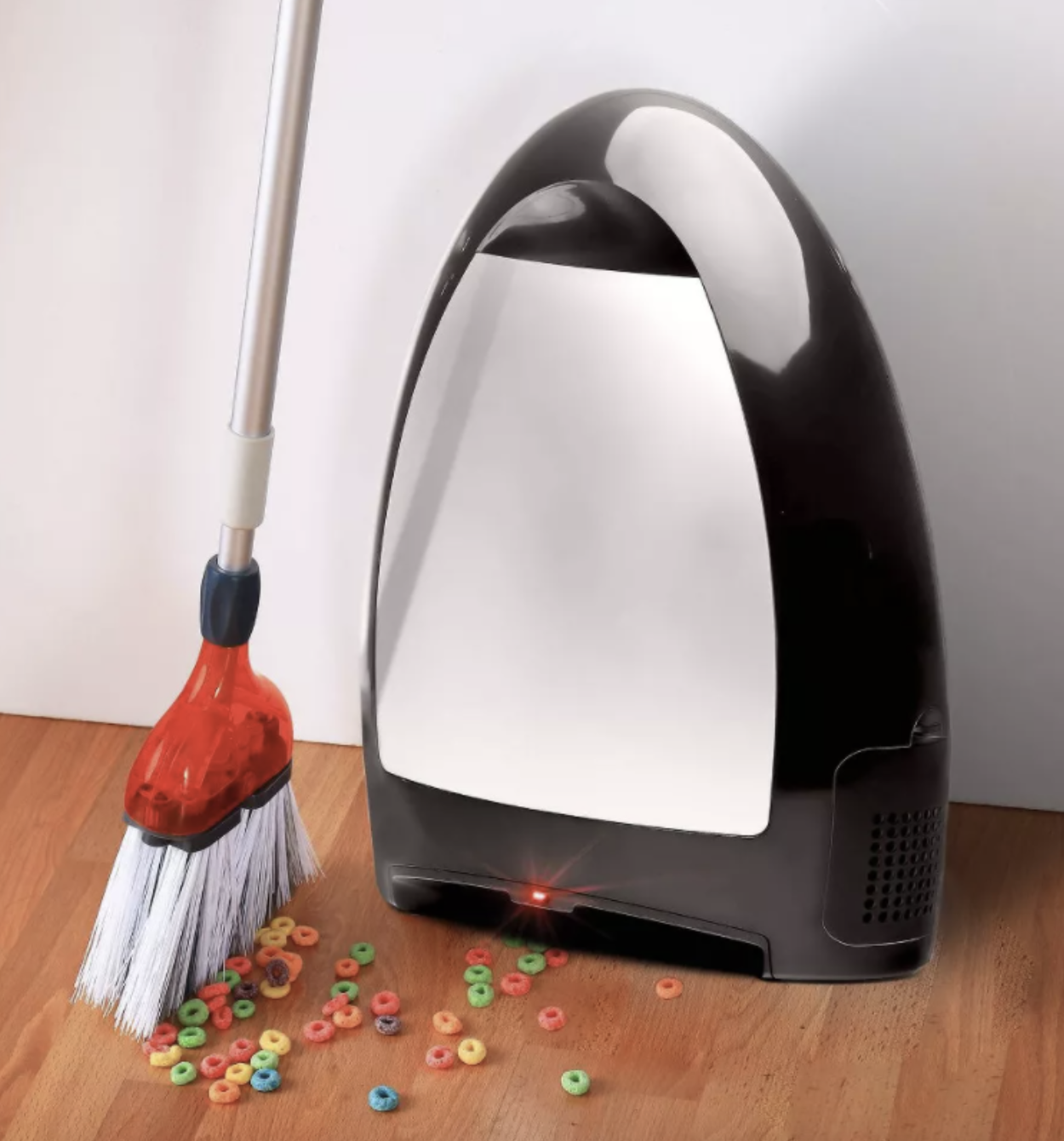 broom brushing cereal on floor into vaccuum