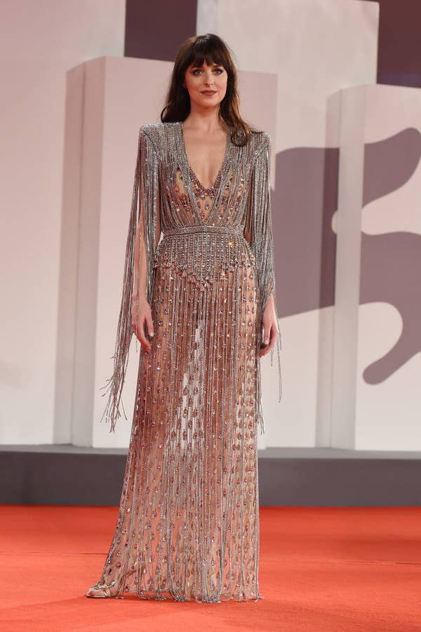 """Dakota Johnson wears a sheer silver gown on the red carpet for """"The Lost Daughter"""""""