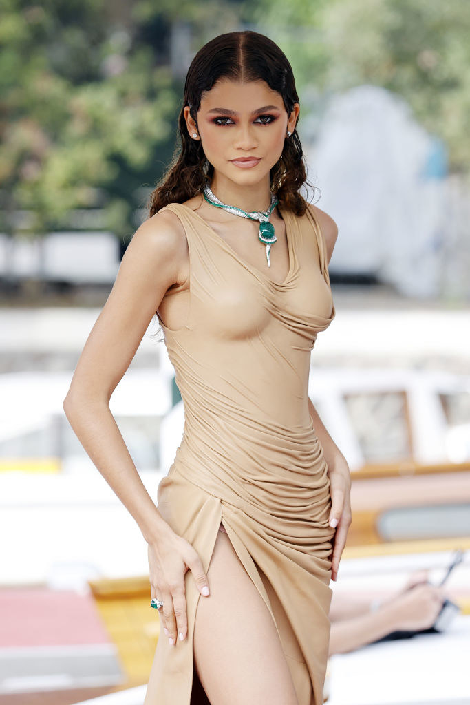 Zendaya is wearing a form-fitting draped leather dress with a thigh-high slit