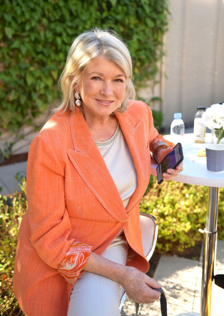 Shot of Martha sitting on a chair outside, she's wearing a bright orange blazer and cream-colored shirt and pants, her phone is in her hand