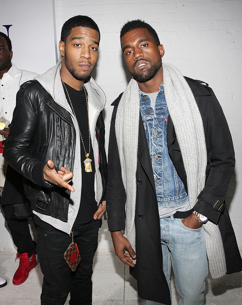 Photo of Kid Cudi with Kanye, both wearing layered clothing and jeans