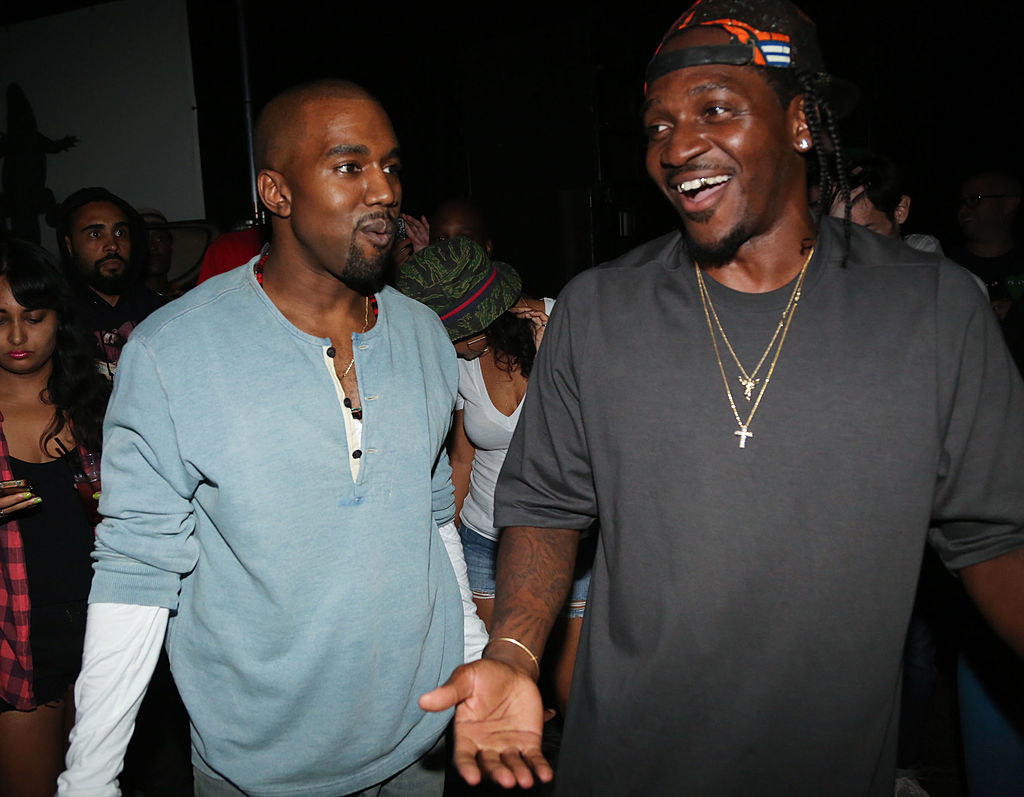 Photo of Kanye and Pusha at a party, the former wears a light blue shirt and the latter wears a black sweater and backwards snapback