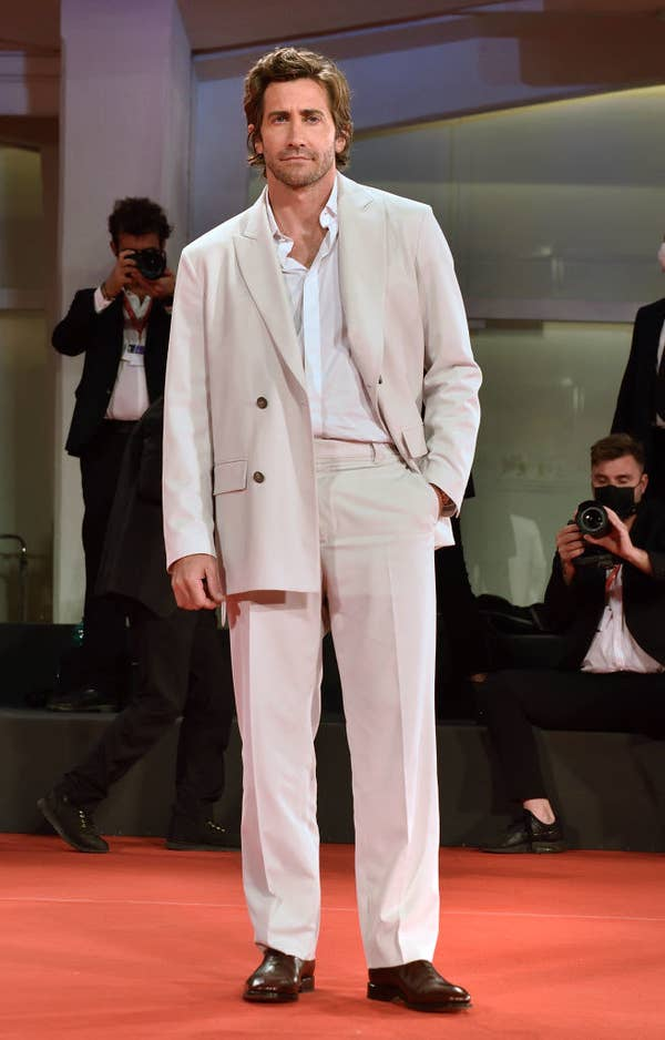 """Jake Gyllenhaal in an all cream-colored tailored suit with brown dress shoes on the red carpet for """"The Lost Daughter"""""""