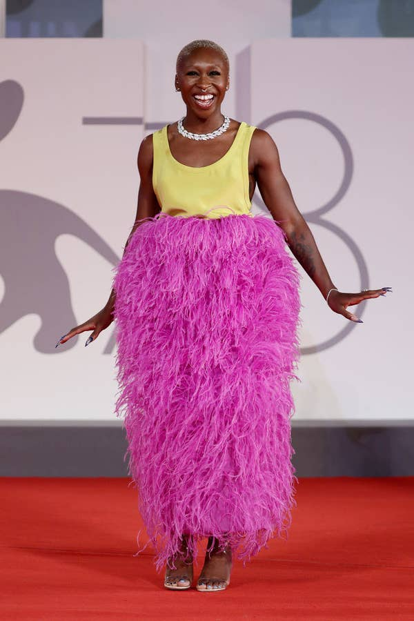 """Cynthia Erivo in a feathered magenta and bright yellow calf-length dress for the red carpet of """"Last Night In Soho"""""""