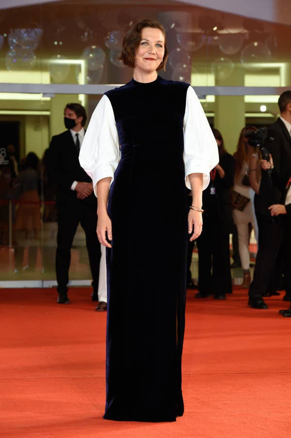 """Maggie Gyllenhaal in a navy plush velvet gown with white sleeves on the red carpet for """"The Lost Daughter"""""""