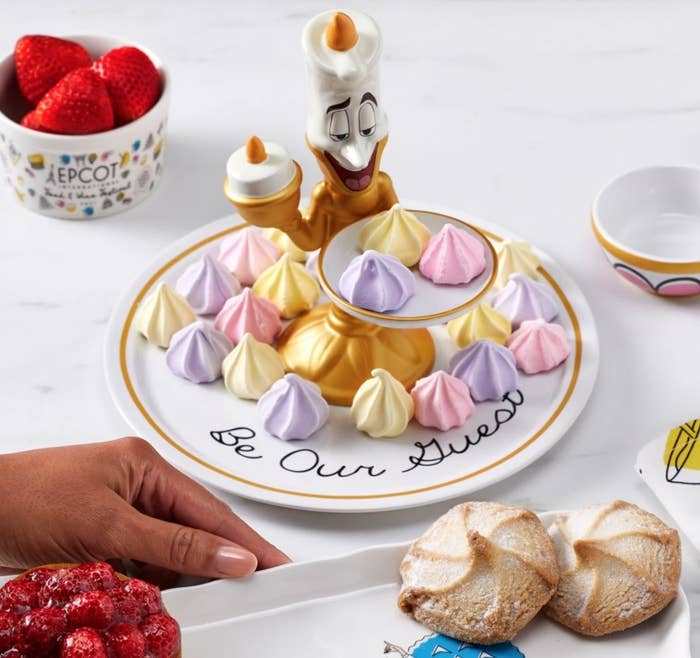 white plate with the words Be Our Guest with a ceramic Lumiere holding a smaller white plate