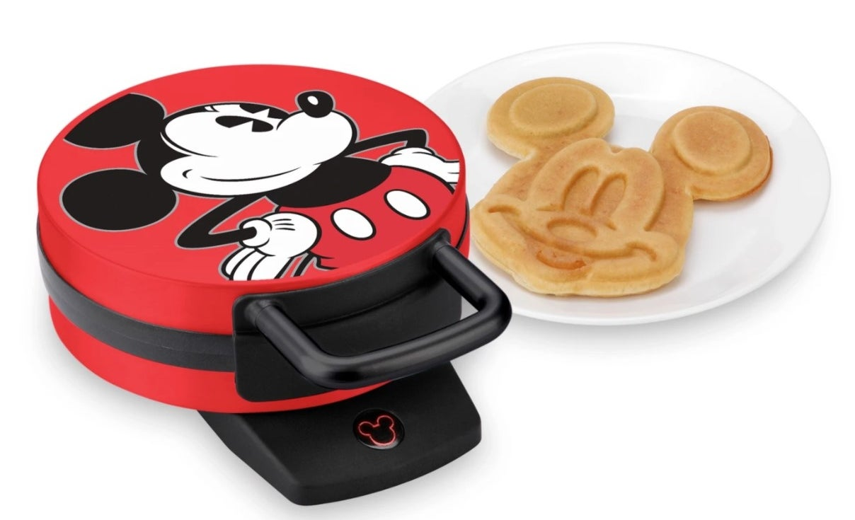 A Mickey-shaped waffle maker with red outside and Mickey image