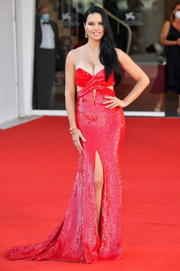 """Adriana Lima in a sparkly red gown with cutouts beneath the bust on the red carpet for """"Madres Paralelas"""""""
