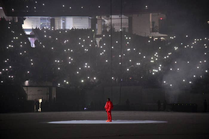 kanye west wearing all red standing in the middle of a stadium