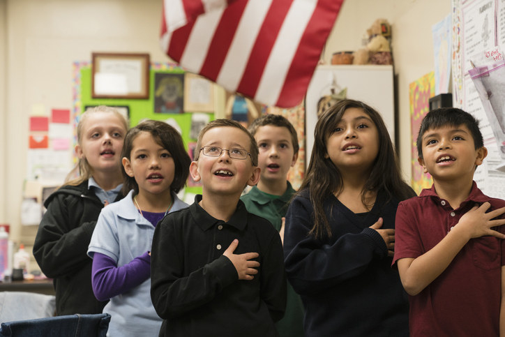 Kids doing the pledge of allegiance to the U.S. flag in a classroom