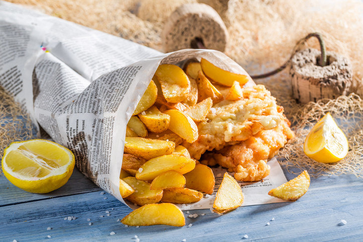 Fish and chips wrapped in newspaper with lemon wedges