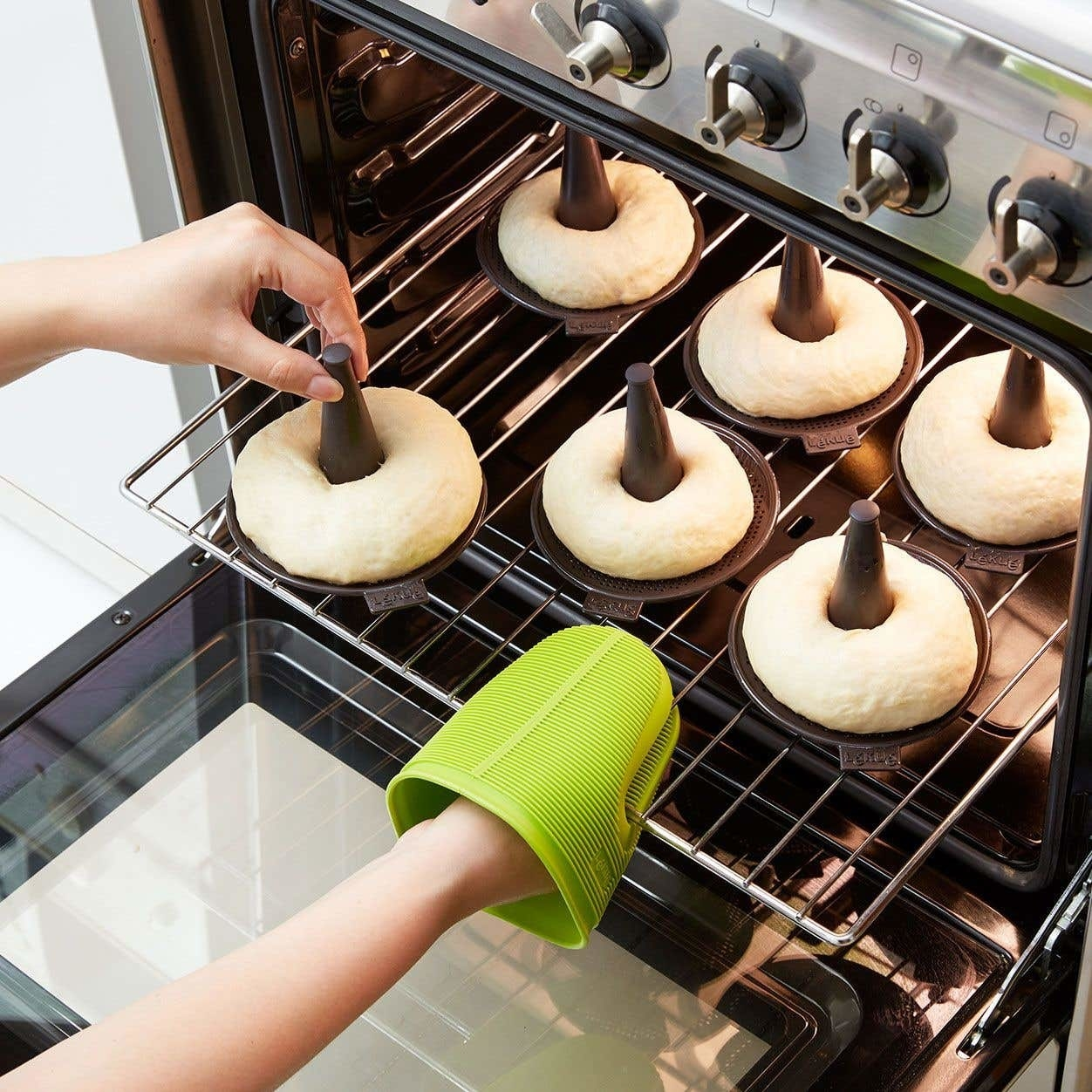 A person placing a bunch of bagels in the oven