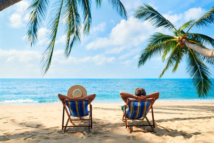 Two people in lounge chairs on a beach with their arms behind their back