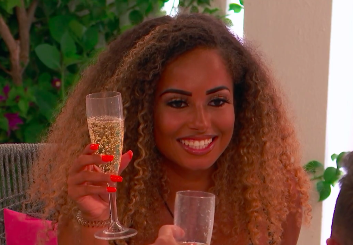 Amber smiling and holding a champagne glass