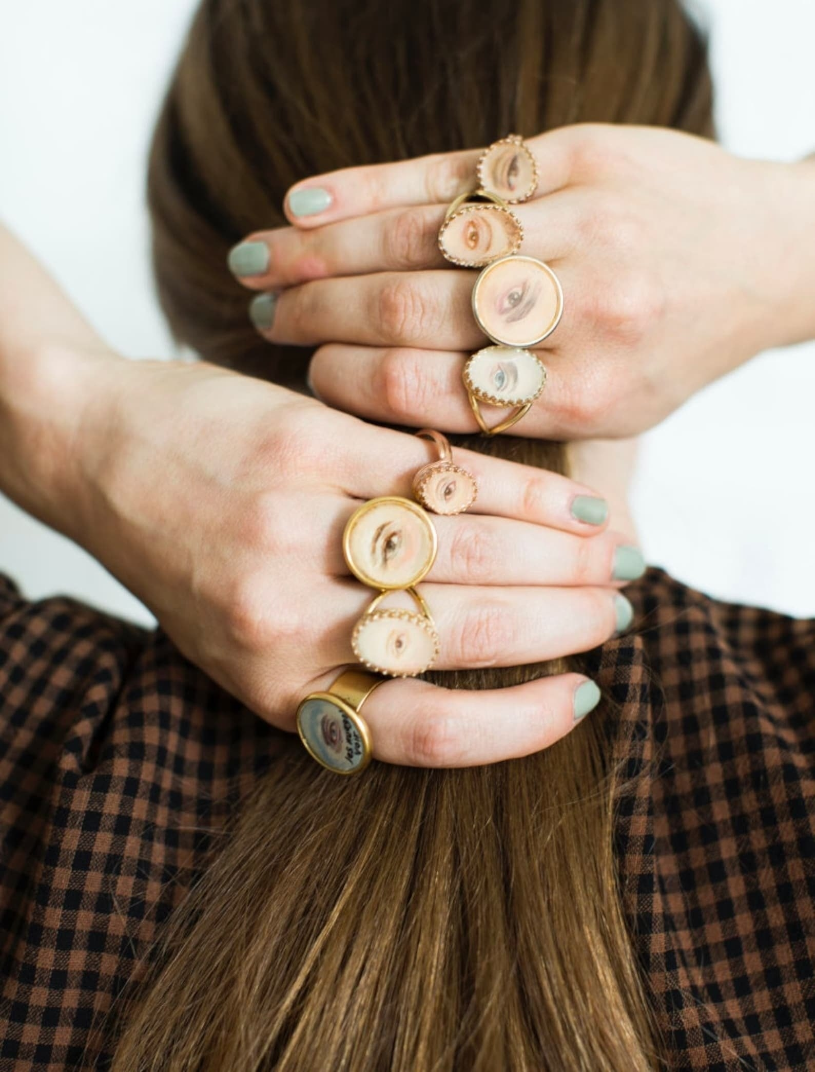 back of person's head with their hands holding their hair. every finger has a different vintage ring with a portrait of an eye.
