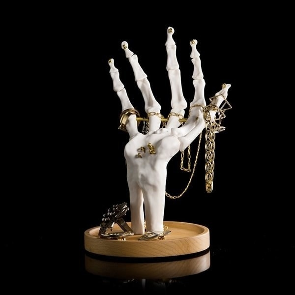 skeleton hand on a wood base with lots of jewelry on the fingers