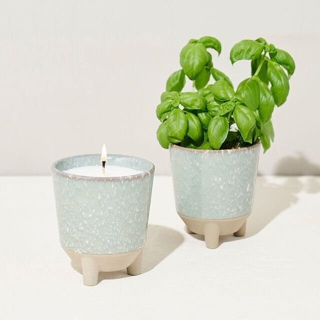 two ceramic pots with three legs. one is being used as a candle and the other is filled with herbs.