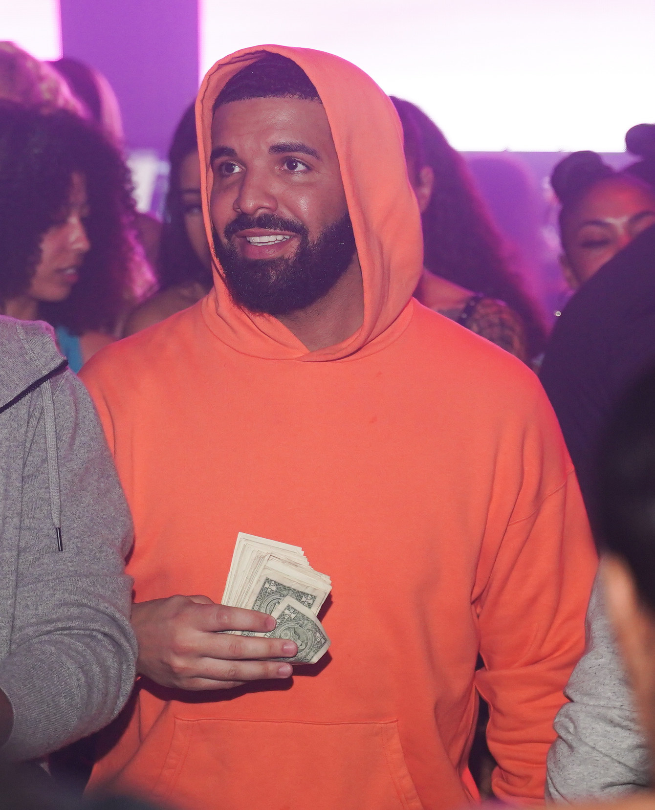 Drake in a hoodie and holding a roll of bills